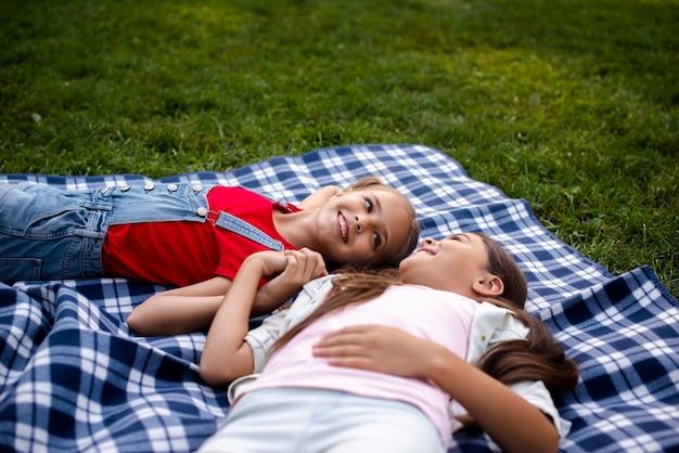 Meninas do smiley no cobertor juntos de mãos dadas Foto gratuita