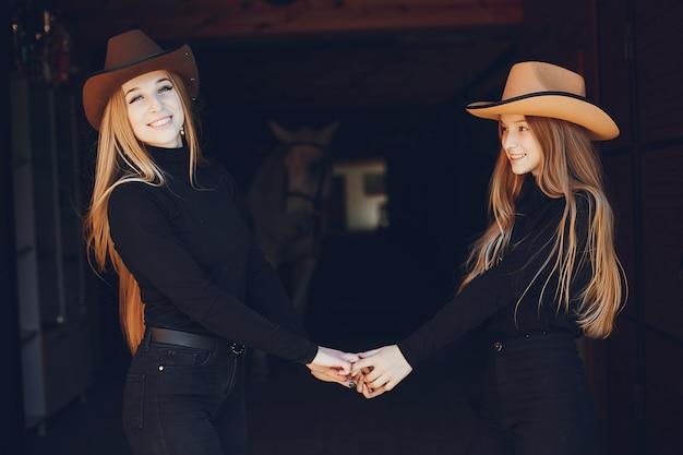 Meninas elegantes com um cavalo em uma fazenda Foto gratuita