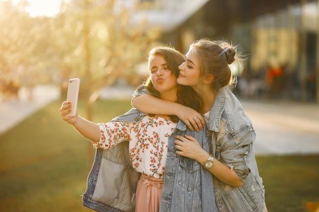 Meninas elegantes e com estilo em um parque de verão Foto gratuita