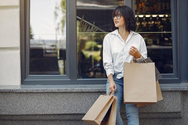 Meninas elegantes e elegantes na rua com sacolas de compras Foto gratuita