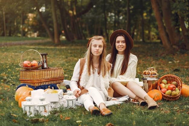 Meninas elegantes e elegantes, sentado em um parque Foto gratuita