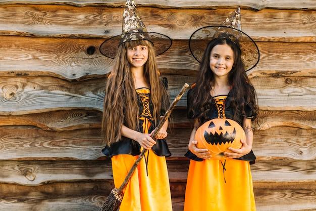 Meninas, em, dia das bruxas, trajes, com, vassoura, e, abóbora, olhando câmera Foto gratuita