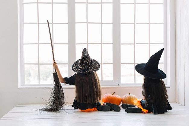 Meninas em trajes de halloween com vassoura sentado perto da janela Foto gratuita