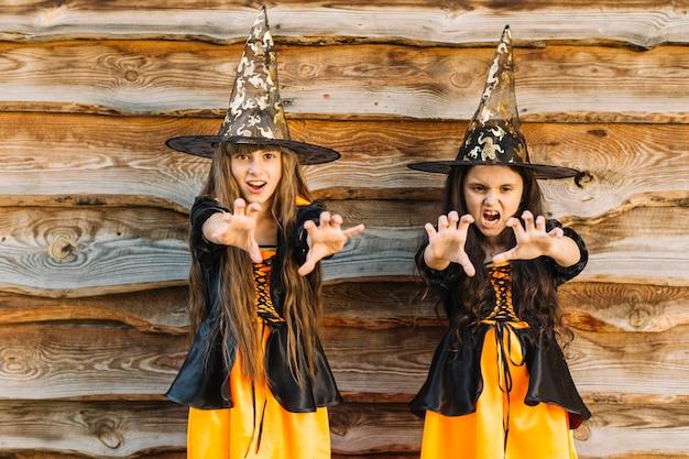 Meninas em trajes de halloween, fingindo magia Foto gratuita