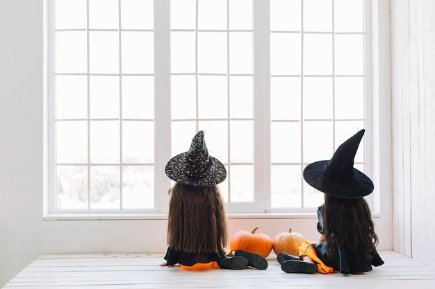 Meninas em trajes de halloween, sentado perto da janela Foto gratuita