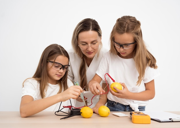 Meninas fazendo experimentos científicos com professora e limões Foto gratuita