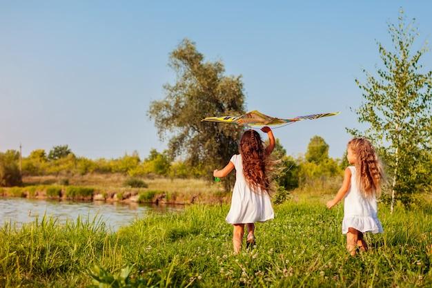 Meninas felizes com pipa correndo no prado. crianças se divertindo brincando ao ar livre Foto Premium