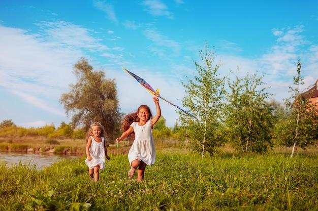 Meninas felizes com pipa correndo no prado no parque de verão, crianças se divertindo brincando Foto Premium