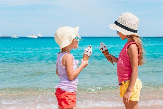 Meninas felizes comendo sorvete durante as férias de praia. Foto Premium