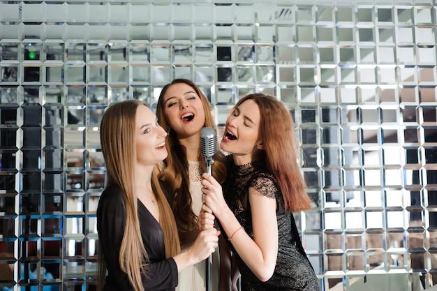 Meninas felizes se divertindo cantando em uma festa Foto Premium