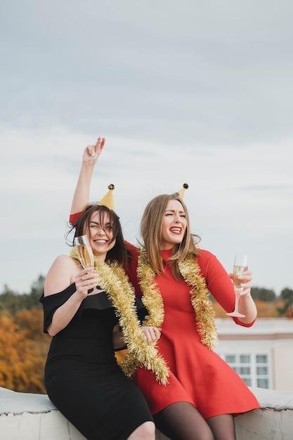 Meninas festejando no topo do telhado Foto gratuita