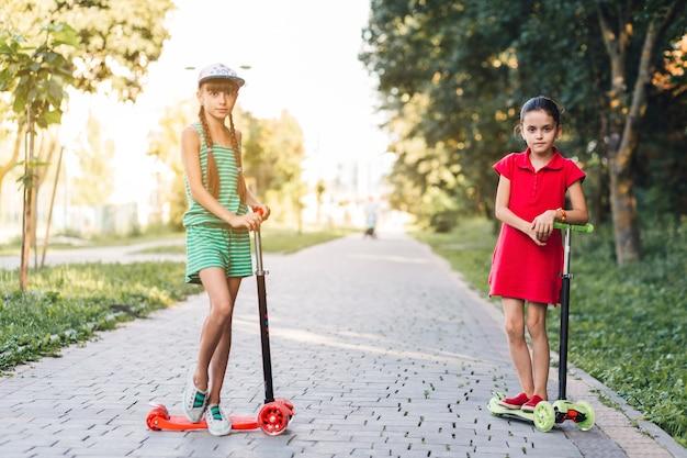 Meninas, ficar, com, scooter, ligado, pavimento Foto gratuita
