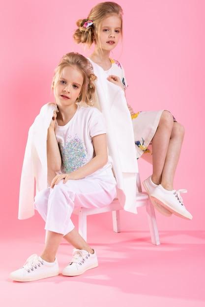 Meninas gêmeas em roupas brilhantes, posando perto da escada com duas etapas na rosa. Foto Premium