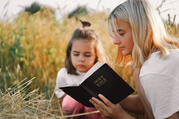 Meninas lendo a bíblia sagrada em um campo de trigo. estudem a bíblia sagrada juntos. Foto Premium
