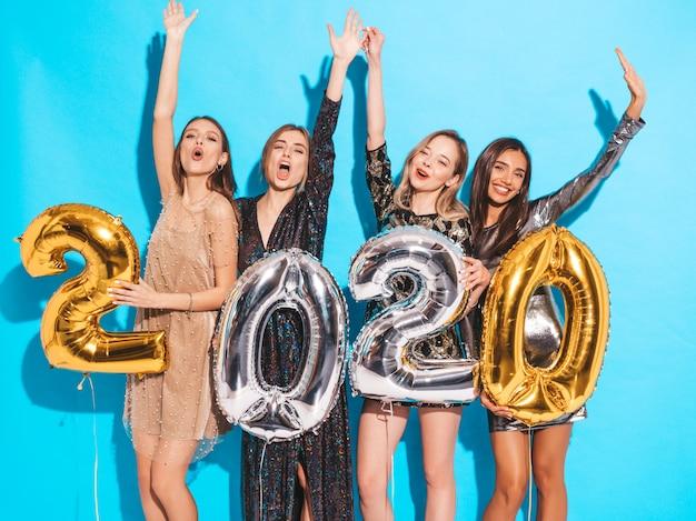 Meninas lindas felizes em elegantes vestidos de festa sexy segurando balões de ouro e prata 2020 Foto gratuita
