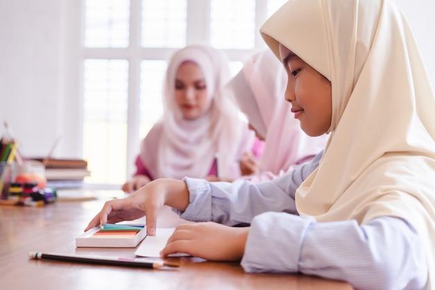 Meninas muçulmanas asiáticas bonitos que pintam e que desenham na sala de aula. Foto Premium