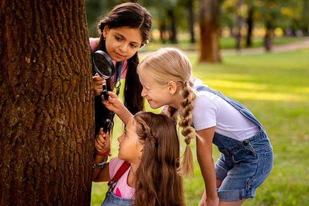 Meninas, olhando para o caule da árvore através da lupa Foto gratuita