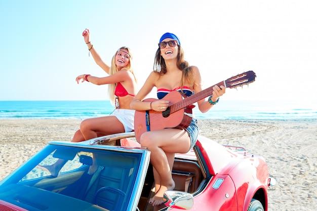 Meninas se divertindo tocando violão na praia de th em um carro Foto Premium