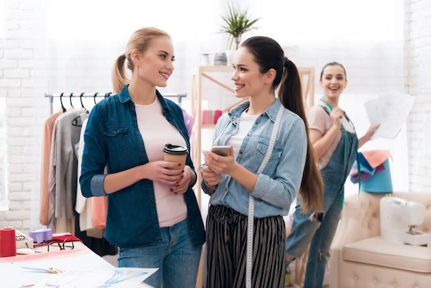Meninas segurando café e telefone olham para o outro Foto Premium
