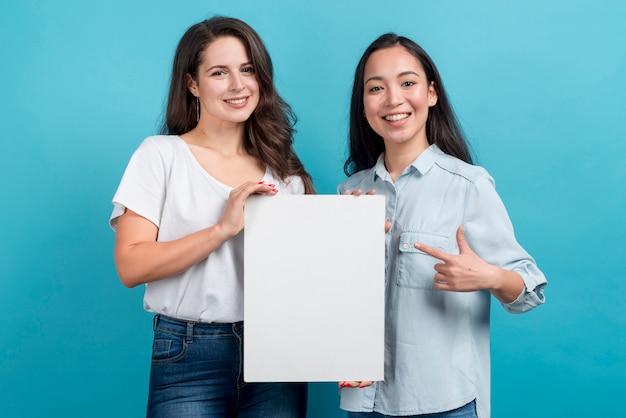 Meninas, segurando, em branco, tábua Foto gratuita