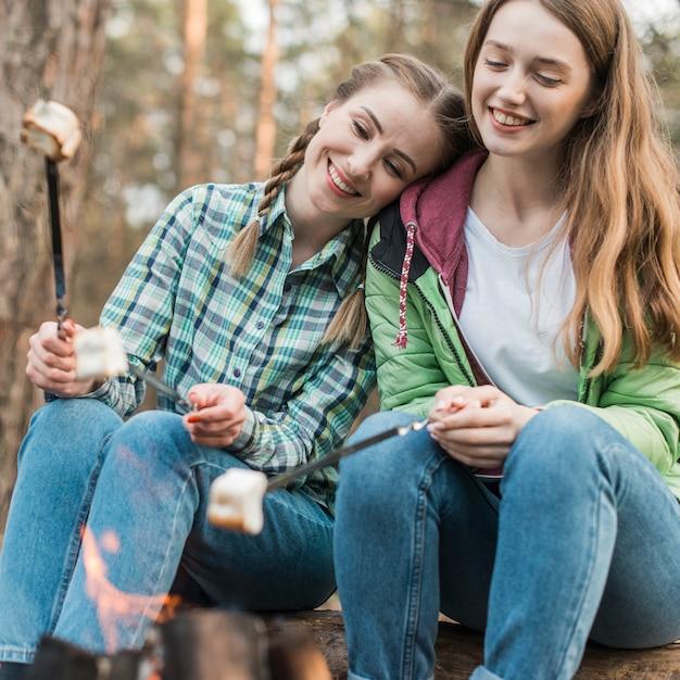 Meninas sorridentes com marshmallow Foto gratuita