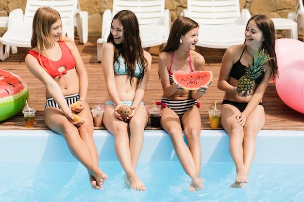Meninas sorrindo um para o outro e segurando frutas Foto gratuita
