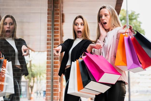 Meninas surpreendidas com sacos de compras, olhando para a janela Foto gratuita
