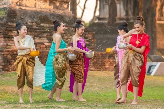 Meninas tailandesas e meninas de laos, salpicos de água durante festival festival songkran Foto Premium