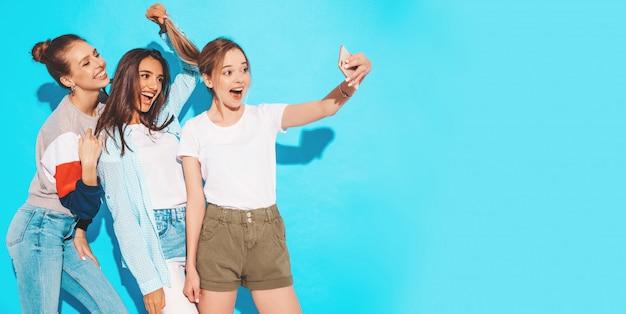 Meninas, tirando fotos de auto-retrato de selfie no smartphone. modelos posando perto de parede azul no estúdio, fêmea, mostrando emoções de rosto positivo Foto gratuita
