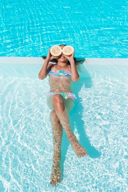 Menininha, cobertura, olhos, com, limão, metades, perto, olhos, ligado, piscina Foto Premium
