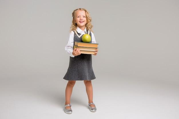 Menininha com livros sobre um fundo claro Foto Premium