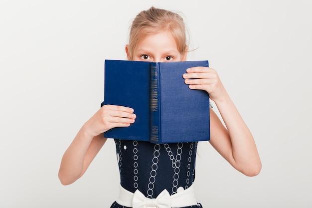 Menininha, com, rosto, atrás de, livro Foto gratuita