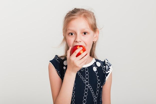 Menininha, comer uma maçã Foto gratuita