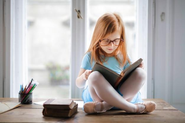 Menininha, lendo um livro Foto Premium