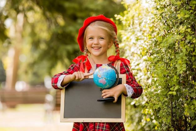Menininha loira primeira série no vestido vermelho e boina segurando uma prancheta vazia e globo Foto Premium