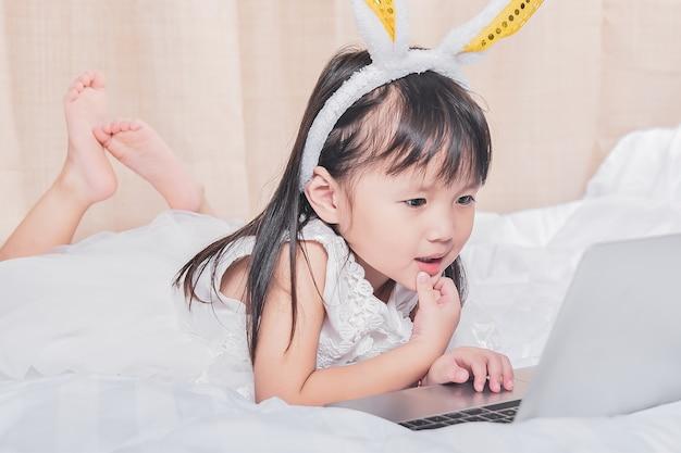Menininha, mentindo, com, laptop, cama, feliz, sorrindo, pensando, com, tecnologia, conceito Foto Premium