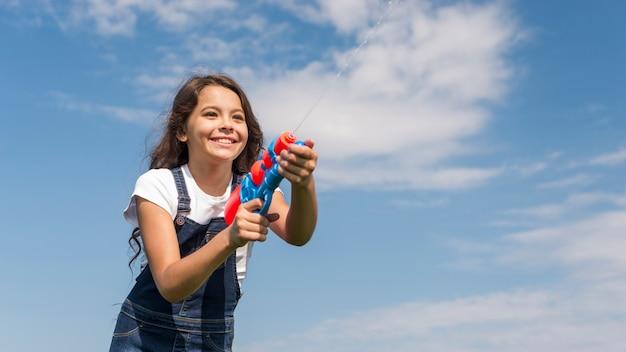 Menininha, tocando, com, injetor água, exterior Foto gratuita