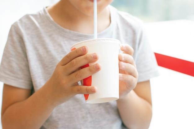 Menino, 8, anos velho, bebidas, coquetel leite, de, copo papel, conceito fast food Foto Premium