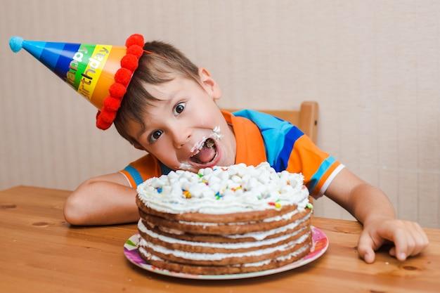 Menino a criança está comendo seu bolo de aniversário. Foto Premium