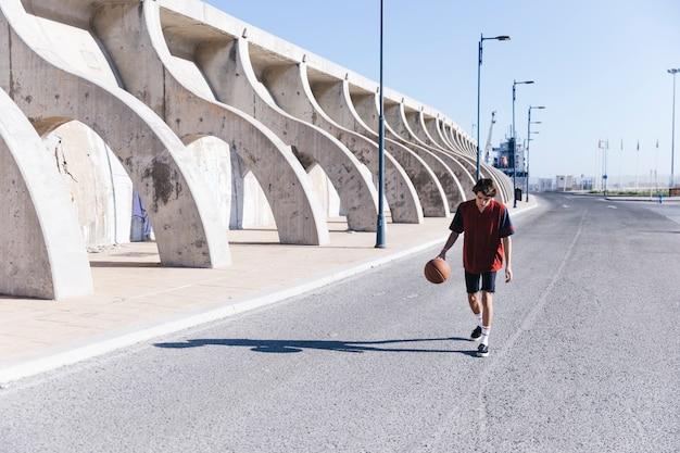 Menino adolescente, andar, rua, com, basquetebol Foto gratuita