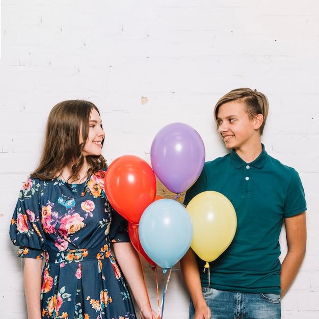 Menino adolescente, e, menina, segurando balões, em, mão, olhando um ao outro Foto gratuita