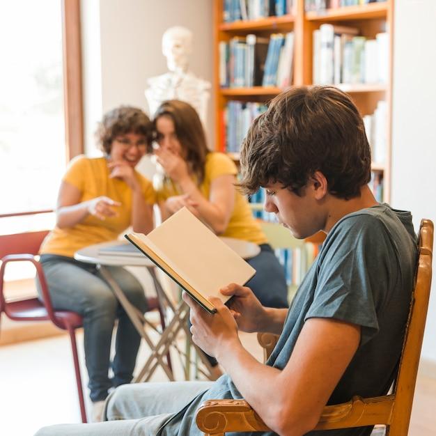 Menino adolescente, livro leitura, perto, bisbilhotar, colegas Foto gratuita