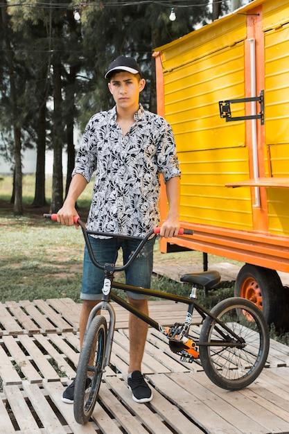Menino adolescente, segurando, seu, bicicleta, em, parque Foto gratuita