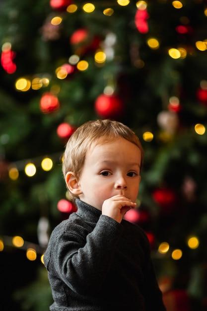 Menino adorável brincando com brinquedos de natal Foto gratuita
