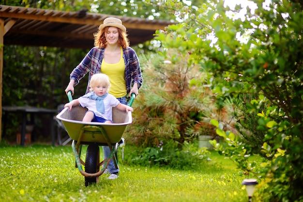 Menino adorável da criança que tem o divertimento em um carrinho de mão que empurra pela mamã no jardim doméstico, no dia ensolarado morno. ativo ao ar livre jogos para crianças no verão. Foto Premium