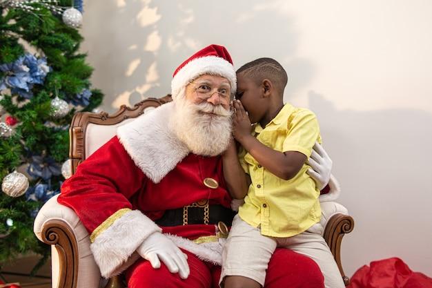 Menino africano sussurrando no ouvido do papai noel Foto Premium
