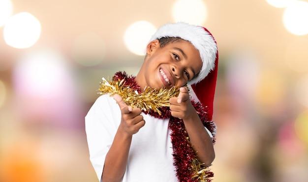 Menino afro-americano com chapéu de natal aponta o dedo para você com uma expressão confiante sobre fundo desfocado Foto Premium