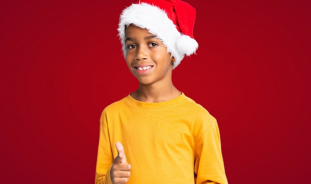 Menino afro-americano com chapéu de natal aponta o dedo para você com uma expressão confiante sobre fundo vermelho Foto Premium