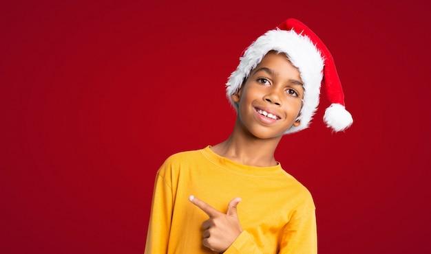Menino afro-americano com chapéu de natal, apontando para o lado para apresentar um produto sobre fundo vermelho Foto Premium