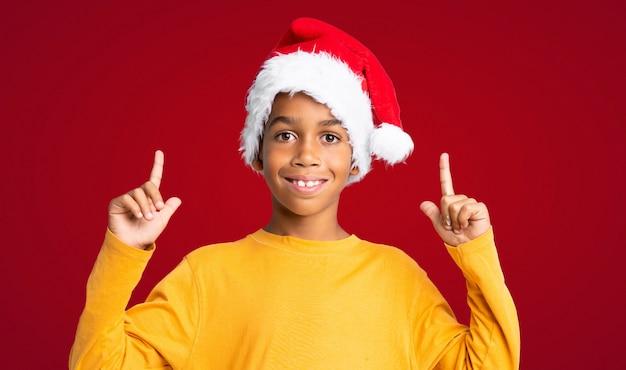 Menino afro-americano com chapéu de natal apontando uma ótima idéia sobre fundo vermelho Foto Premium